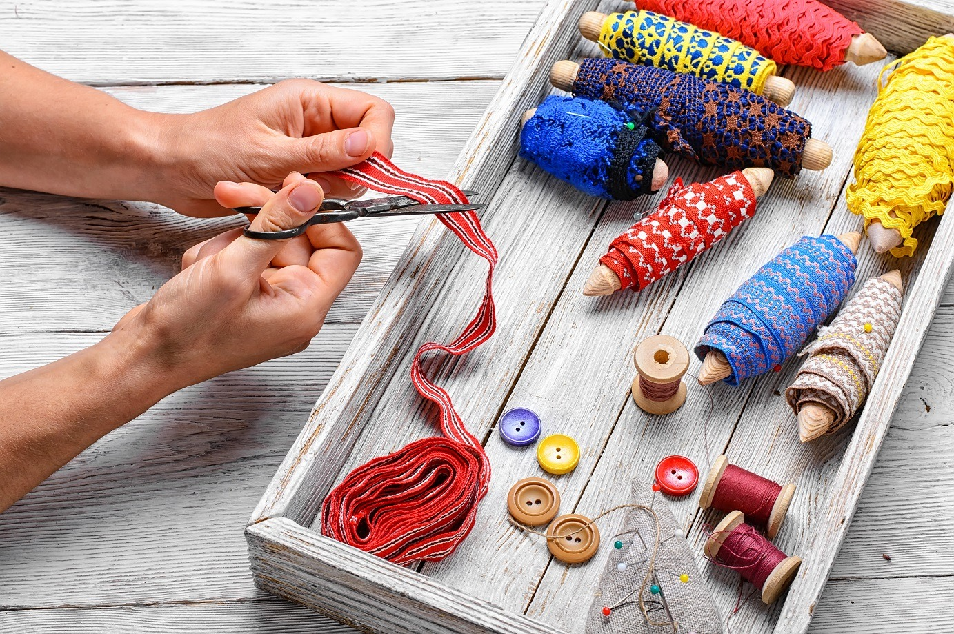 hands of tailor sewing accessories on background thread and buttons