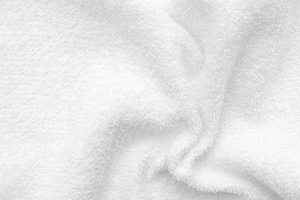 White crumpled terry fabric texture with folds. Towel texture.
