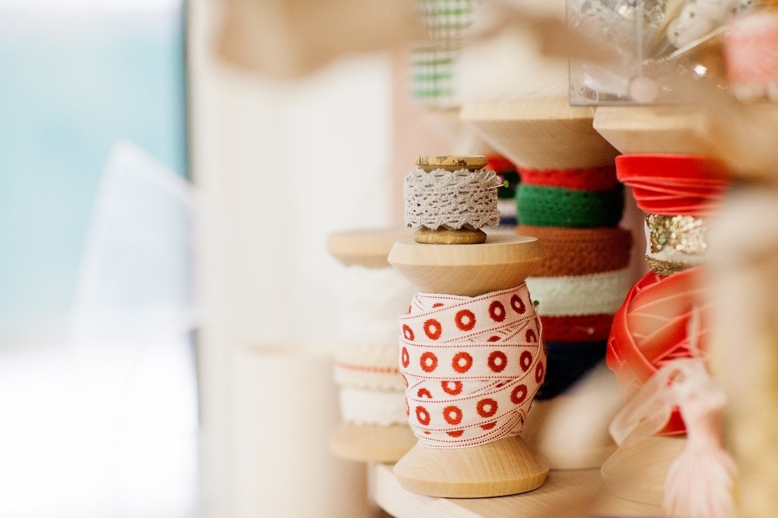 A set of sewing spools with a ribbon is on the desktop